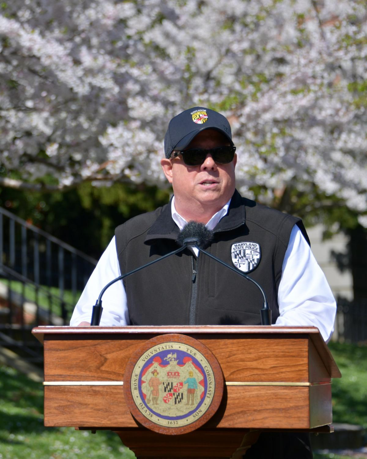 Governor stands at podium outside State House wearing vest_ hat and sunglasses.