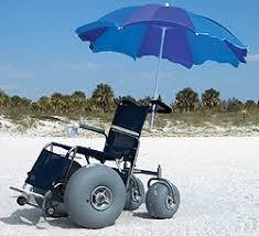 Beach wheelchair with blue umbrella on beach