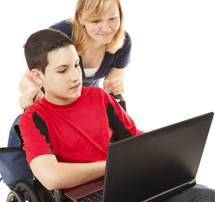 young boy at computer with mother behind him