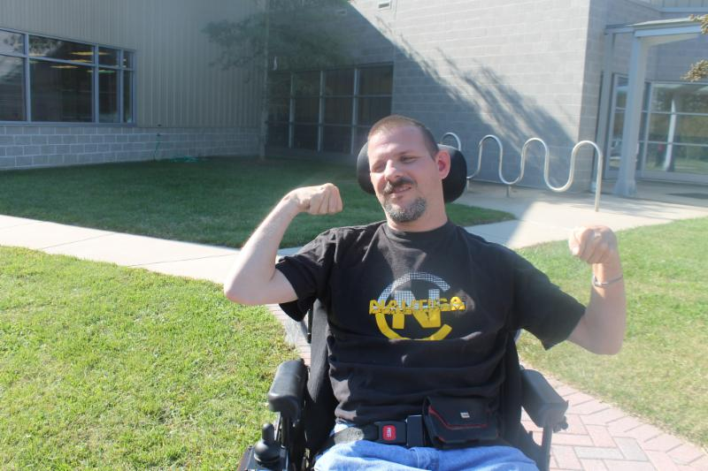 Person in wheelchair makes muscle arm movement