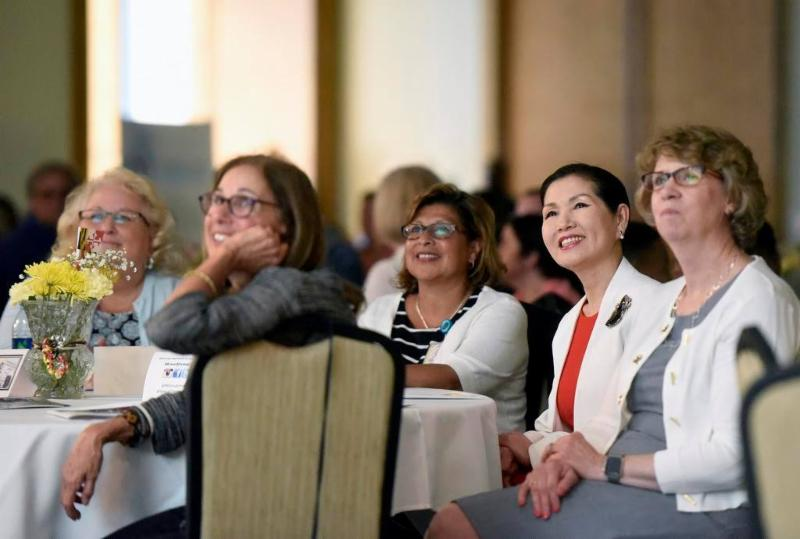 first lady and several women smiling at state