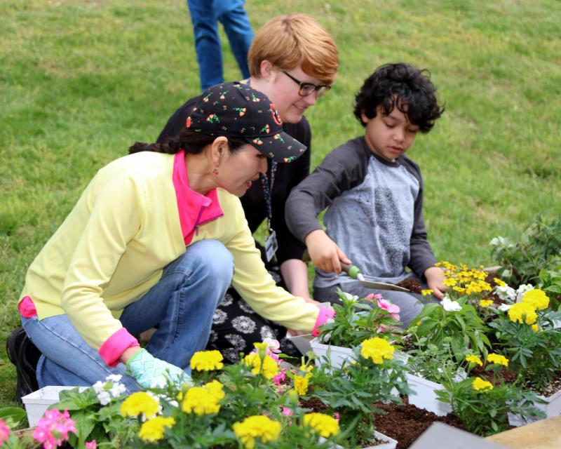 First Lady kneels in garden with student.