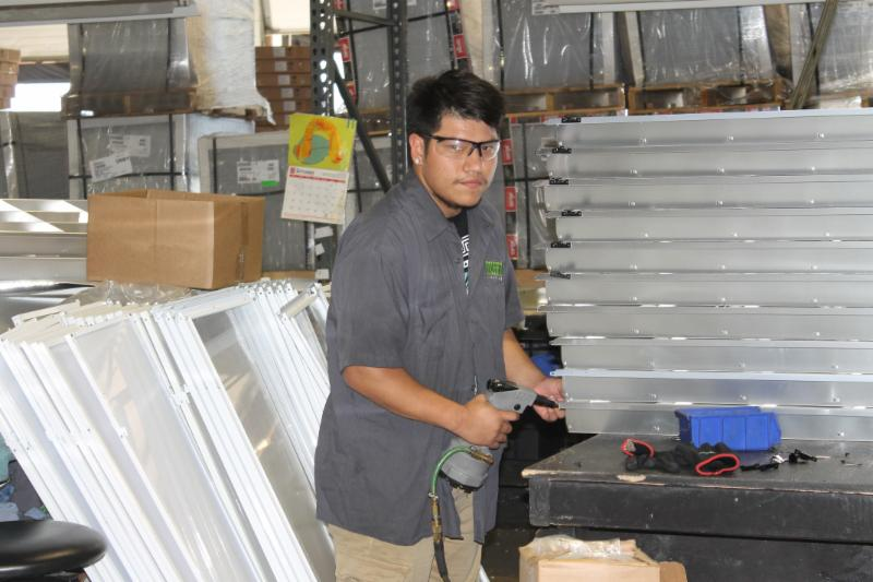 Image of young man with dark hair working in factory