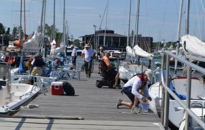 Boat dock with boats on both sides.  Crew members are disembarking using lifts and other accessible devices.