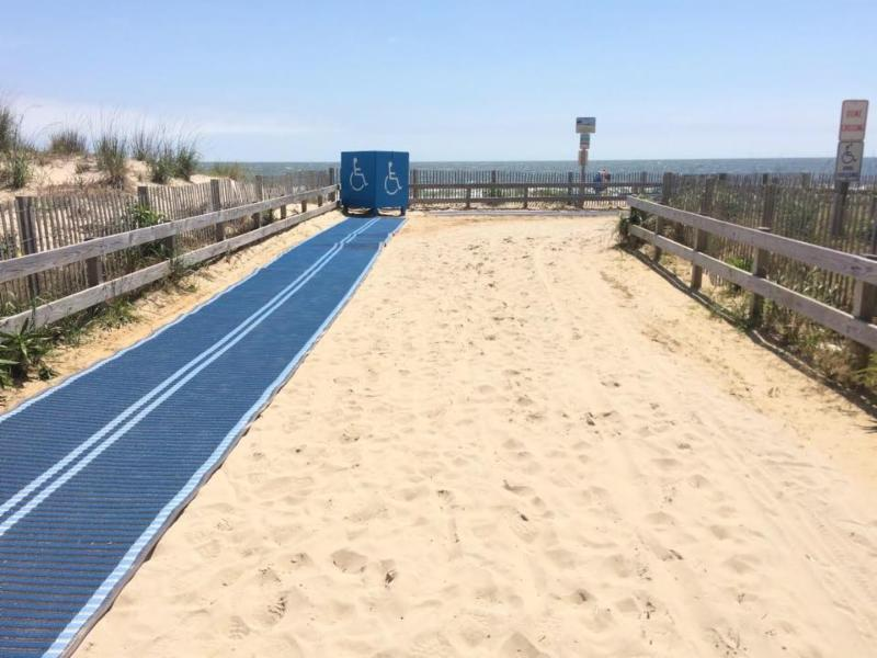 Blue beach mats on dune crossover with wheelchair box at corner