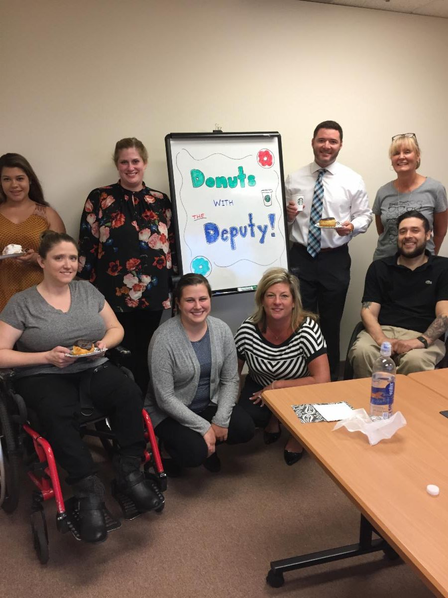 Deputy Secretary Miele stands with 7 staff members from ARI around sign saying _Donuts with the Deputy_