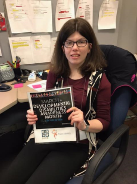 Bridget at her work place holding up a sign for DD awareness month