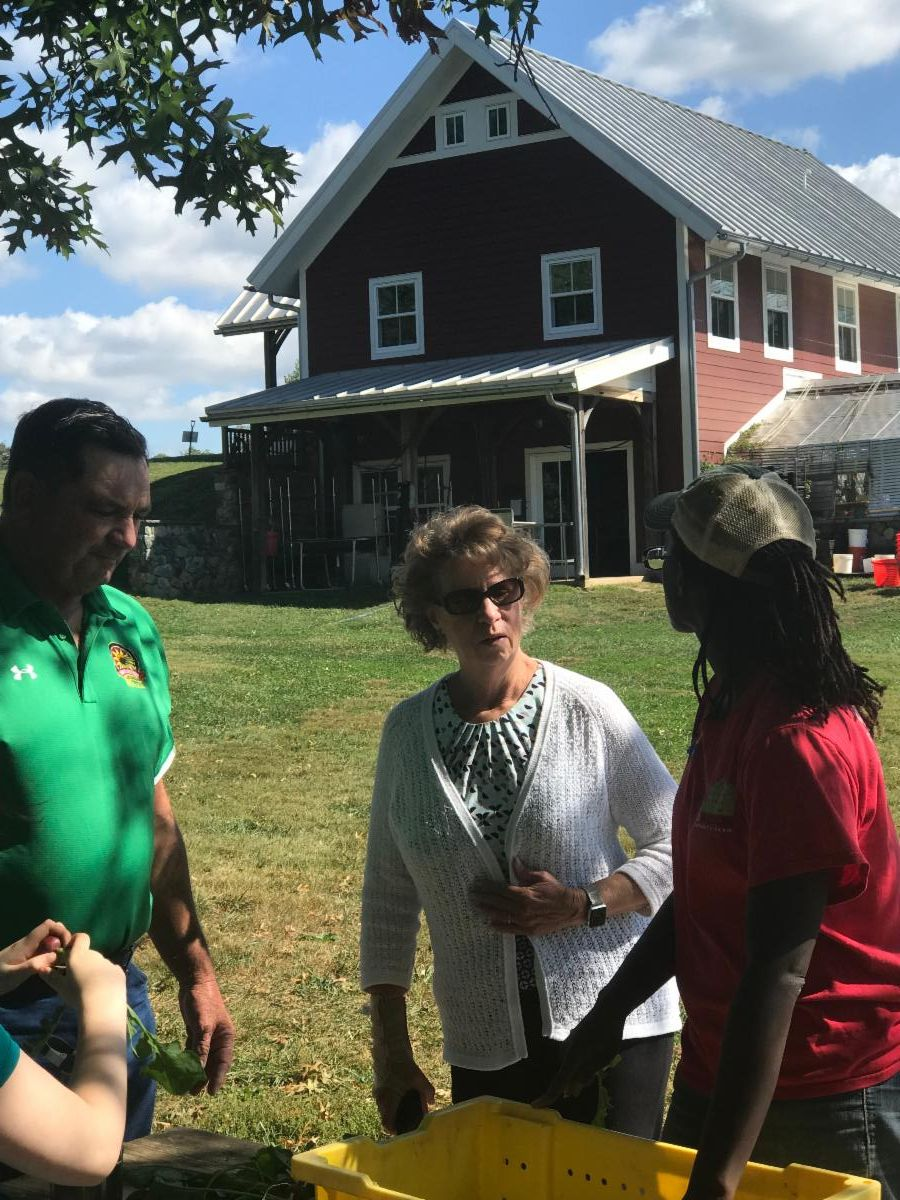 Sec Beatty and Sec Bartenfelder talk to farm worker in front of barn as she sorts veggies.