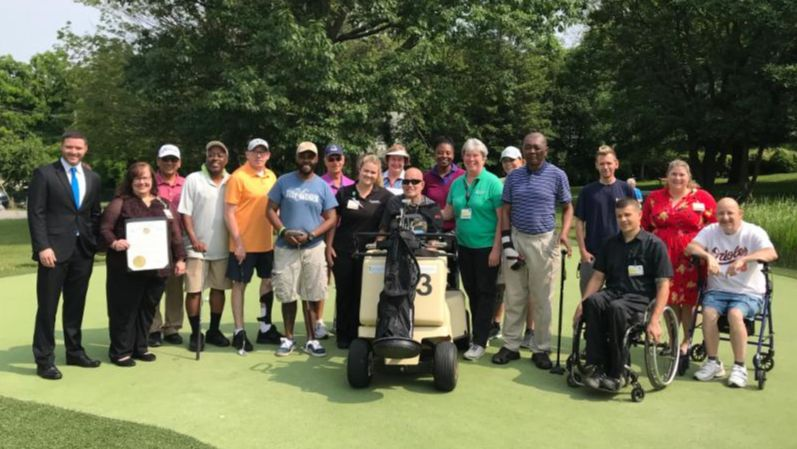 Large group on putting green. Dep Secretary Miele presents Governor_s Citation to staff.