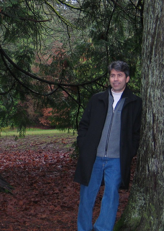Chris Aesoph a white middle-age man leaning against tree trunk