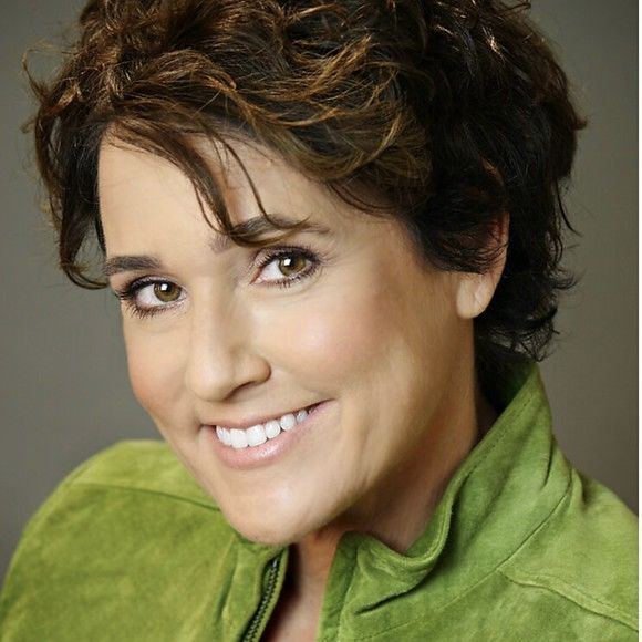 Headshot of a middle age woman with brown hair wearing a green suede jacket