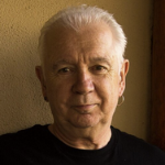 Head shot of man with white hair light skin and earring wearing a black tee shirt.