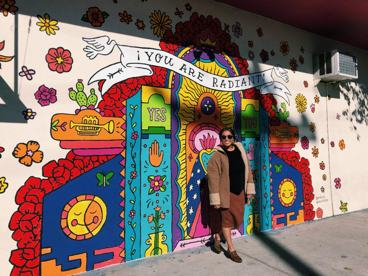 """Erendira standing in front of a mural that says, """"YOU ARE RADIANT"""""""