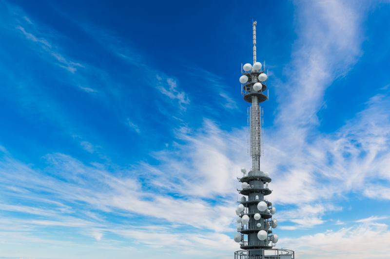 Telecommunications equipment - directional mobile phone antenna dishes. Wireless communication with bright blue sky background.