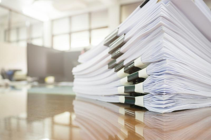 Pile of unfinished documents on office desk. Stack of business paper.