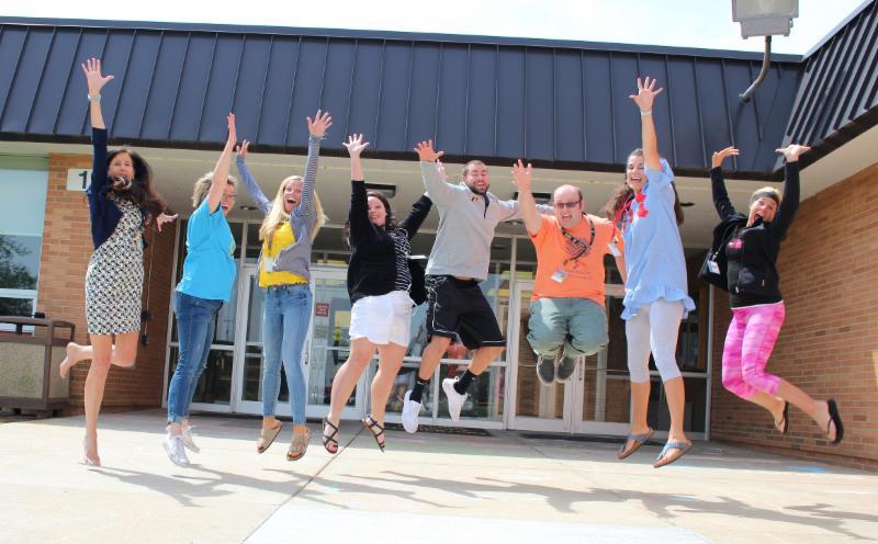 Teachers jumping outside of school