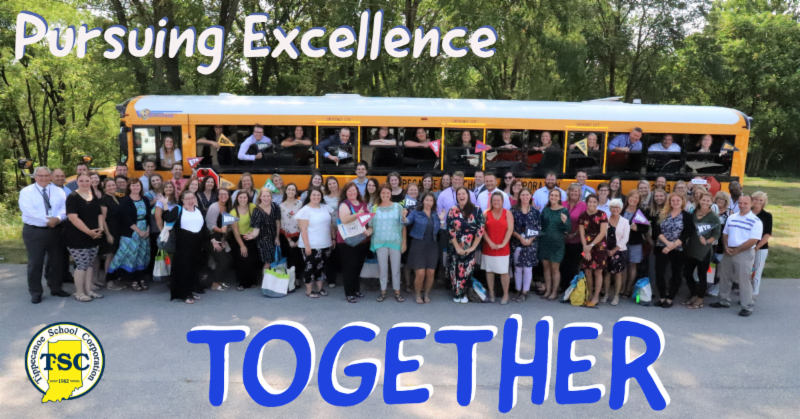 New teachers gather for a picture outside a bus