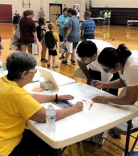 volunteers help families with school supplies and other information