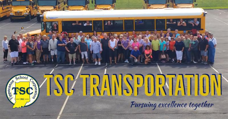 Dozens of bus drivers stand outside a bus for a photo