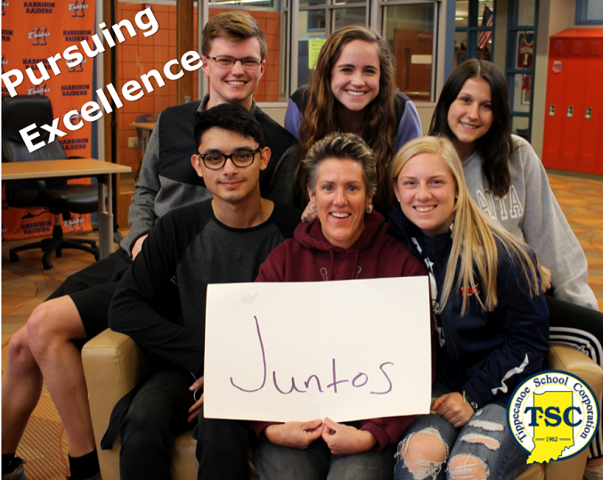 Spanish teacher Jill Mansilla holds a sign that reads Juntos (together) surrounded by students.