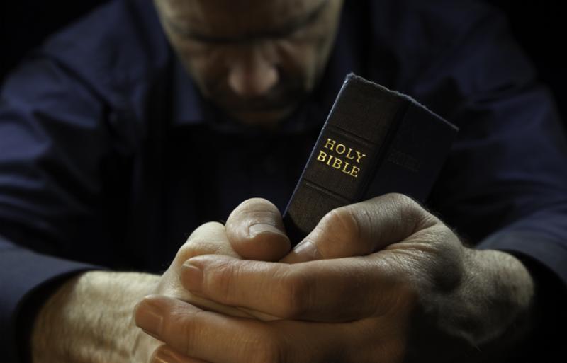 man_praying_holding_bible.jpg