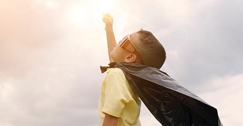 boy with a cape and super hero pose