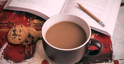 cookie and coffee next to an open book