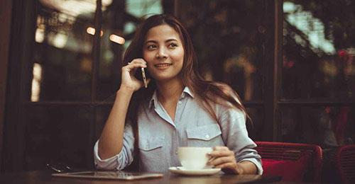 Woman with a coffee on the phone