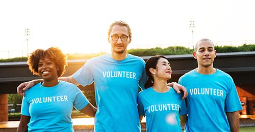 four people standing next to each other wearing blue volunteer shirts