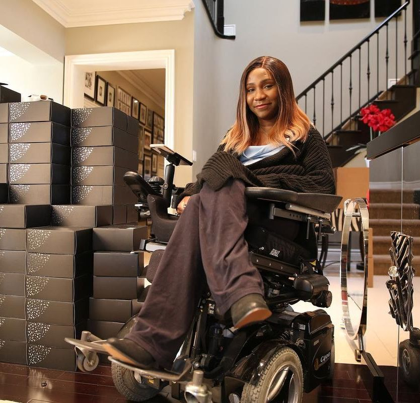 Young woman in wheelchair surrounded by packages.