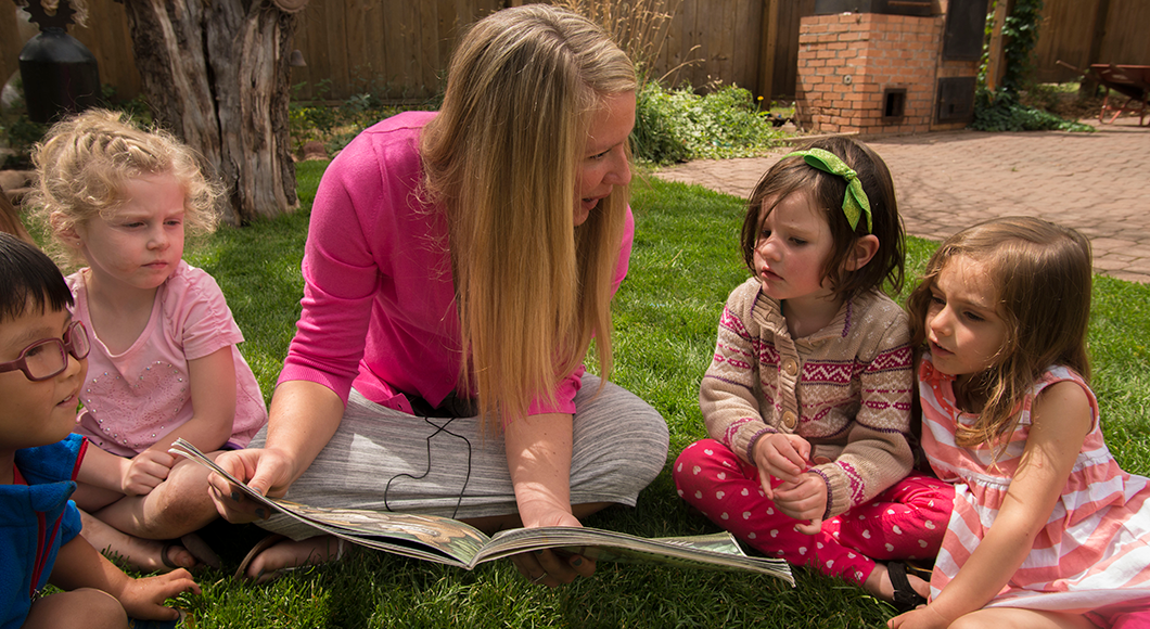 Female preschool teacher sitting on the grass reading to four young students.