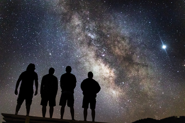 Silhouette of four stargazers in front of the Milky Way galaxy. Photo by Kendall Hoopes.