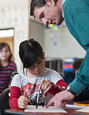Photo: Male, elementary education teacher works with young girl on math problem using a protractor and compass.