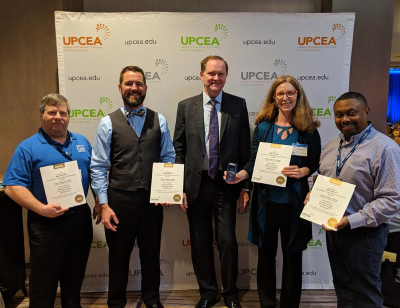 Team members accepting UPCEA Marketing Award with UPCEA president