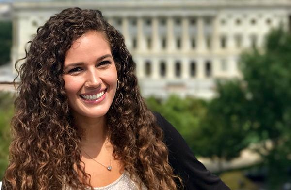 Elizabeth Rule with long brown curly hair smiling with U.S. Capitol building in the background