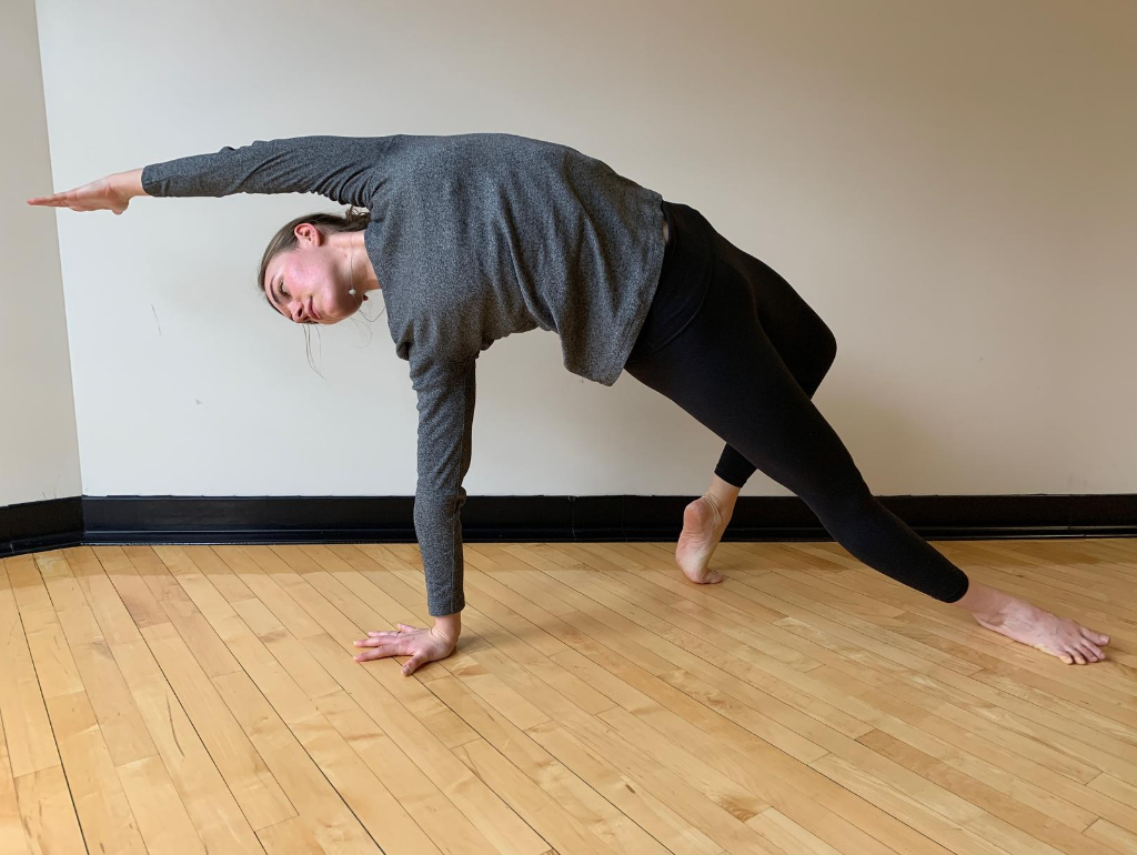 Woman doing a side stretching balance pose with wood floor