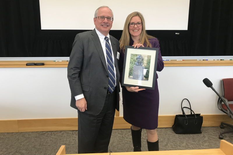 GW President in grey suit on left with Jennifer Wexton in suit with skirt and long blonde hair and glasses holding a framed photo of a George Washington statue at GW