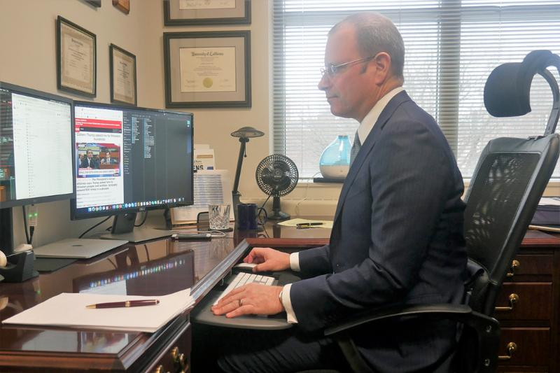 Todd Belt in grey suit with tie sitting at desk looking at computer with Michael Cohen live testimony