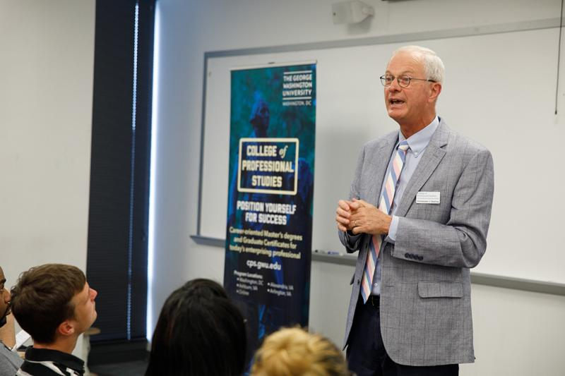 Dean Deering tall man in suit speaks at meet and greet event