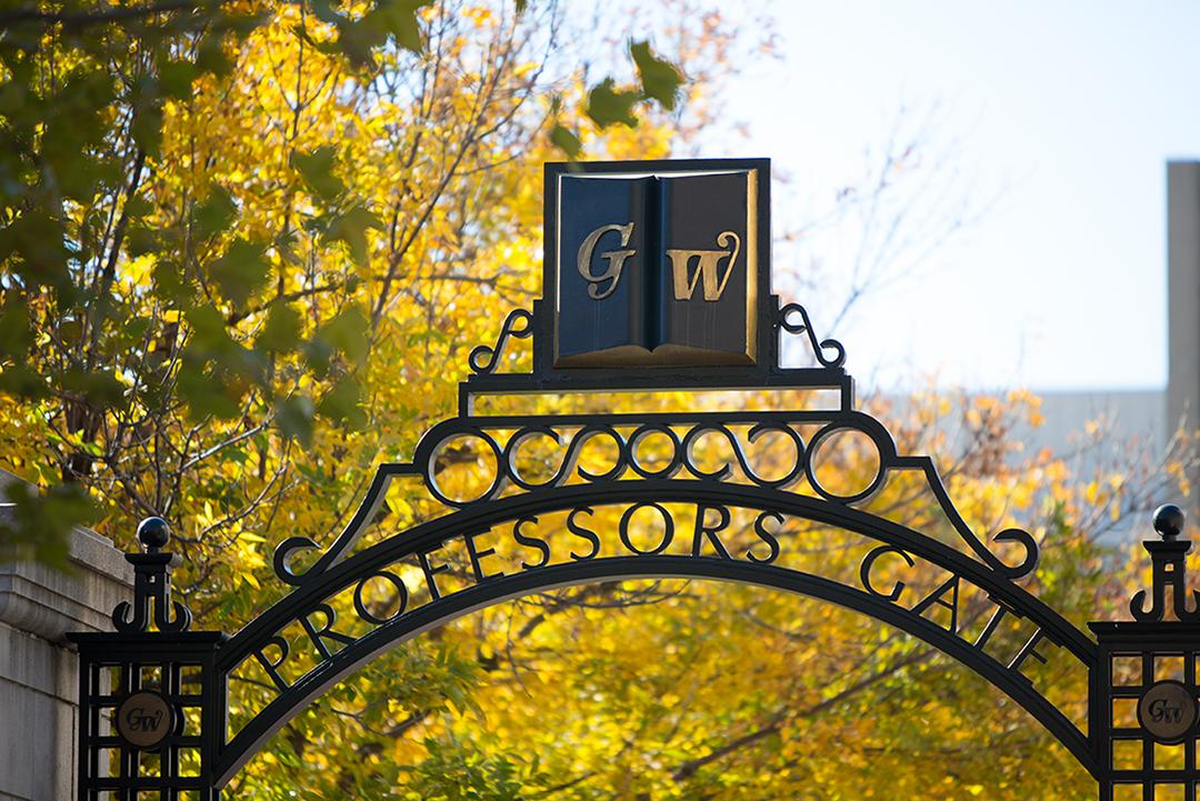 GW Professors Gate in words on the arch between buildings on campus and fall leaves, trees