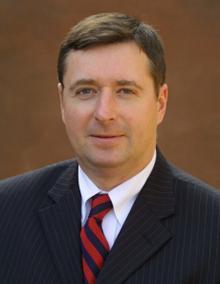 Scott White in dark suit, striped tie