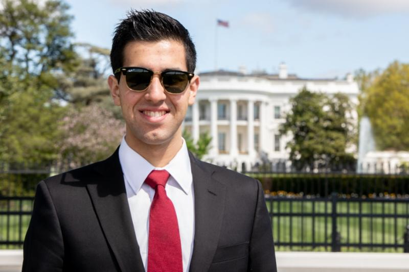 Adam Brown GSPM graduate in front of the White House in a suit and tie
