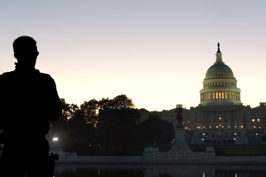 image of security person with back and view of white house at dusk