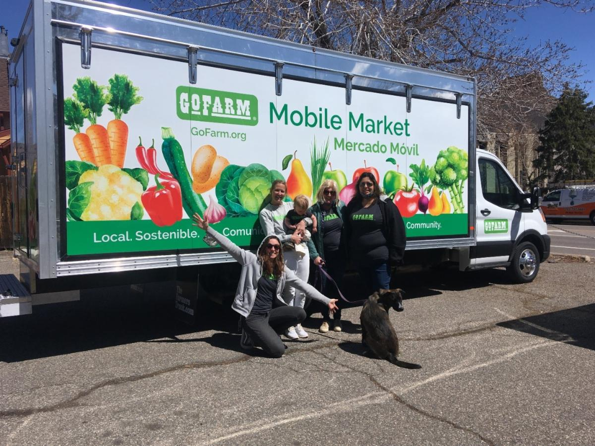 """Pictured: GoFarm's new mobile market (from left to right) Kate Falkenberg (Local Food Share Program Manager), Anna Schott (Program Director) and her son, Eileen O'Rourke (Founder and CEO), and Evelyn Gutierrez (Bilingual Community Liaison) and """"Georgia"""""""