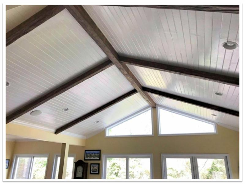 Custom Timber beams over a white planked ceiling.