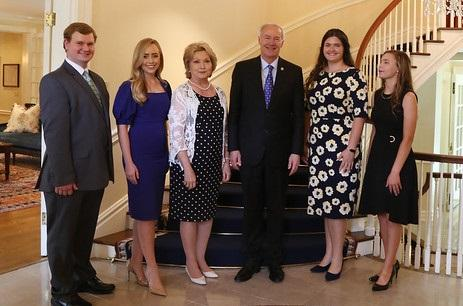 Governor Asa Hutchinson standing with the 4-H finalists in front of a staircase inside the governor's mansion