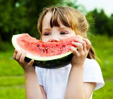 Red-headed girl eating a big slice of watermelon outside