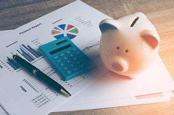 small piggy bank sitting on a desk with a light blue calculator and financial documents