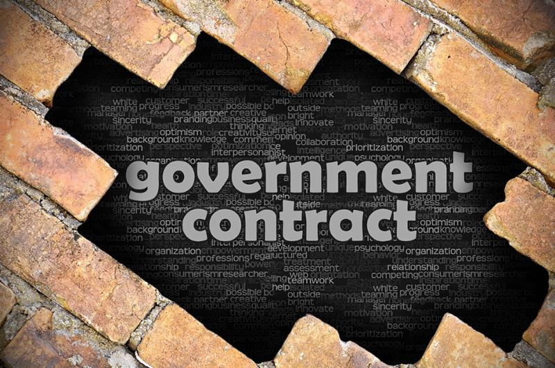 Government Contract surrounded by a brick wall to indicate construction
