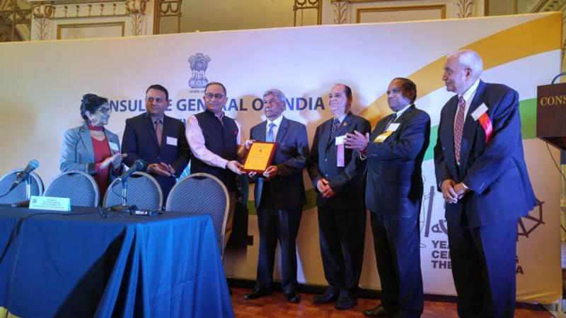 Presentation of a plaque to GOPIO former president Ashook Ramsaran